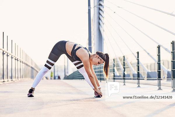 Junge athletische Frau  die sich nach dem Training in der Stadt ausdehnt.