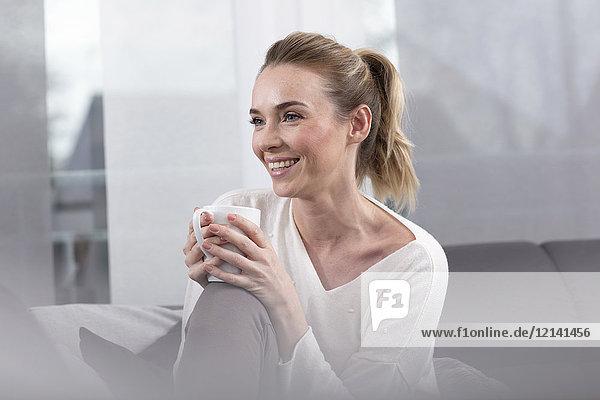 Porträt der glücklichen Frau mit Kaffeetasse zu Hause
