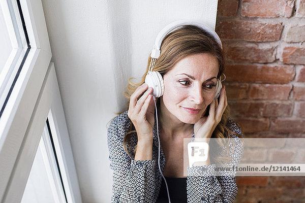 Frau sitzt zu Hause auf dem Fensterbrett und hört Musik.