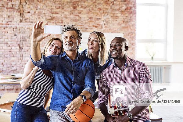 Glückliche Kollegen mit Basketball im Büro  die einen Selfie nehmen
