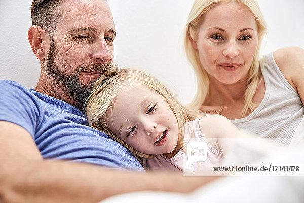 Glückliche Familie im Bett lesen Buch zusammen