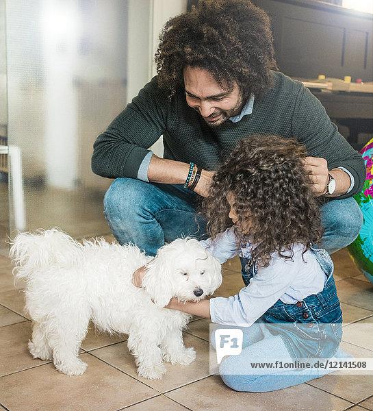Vater und Tochter spielen mit einem kleinen Hund zu Hause