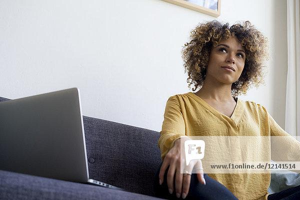 Junge Frau sitzt zu Hause auf der Couch neben dem Laptop