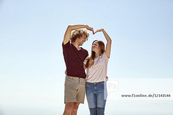 Glückliches junges Paar  das mit den Händen unter blauem Himmel ein Herz formt.
