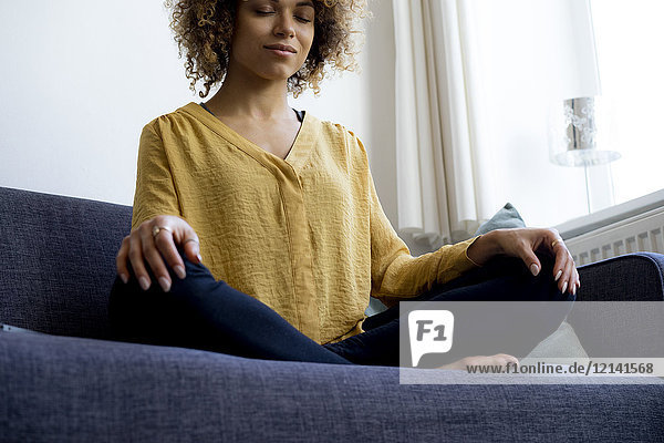 Junge Frau sitzt zu Hause auf der Couch und meditiert.