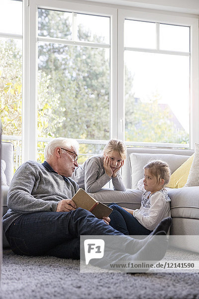 Zwei Mädchen und Großvater beim Lesen im Wohnzimmer