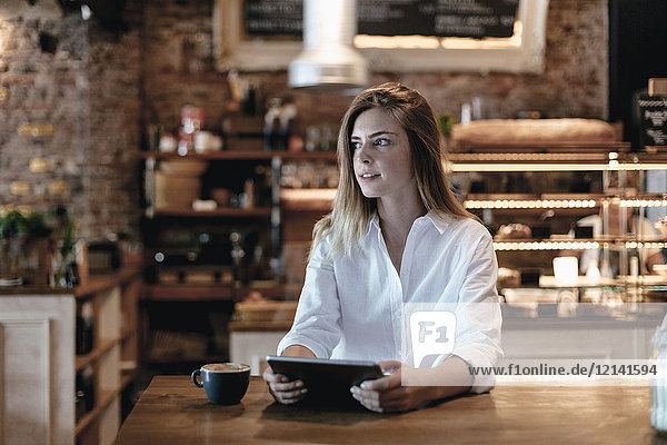 Blond woman sitting in cafe  using tablet  thinking
