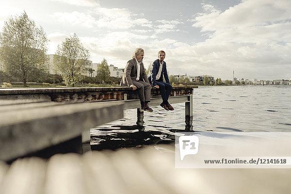 Zwei Geschäftsleute am Steg eines Sees