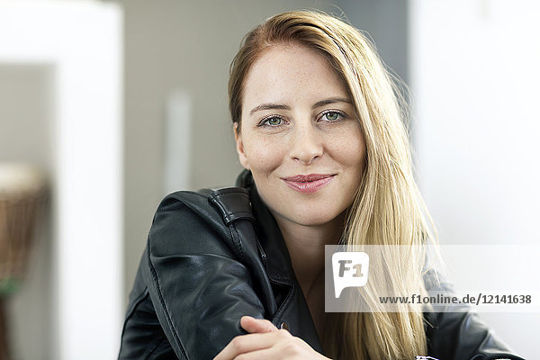 Portrait of smiling young woman wearing leather jacket