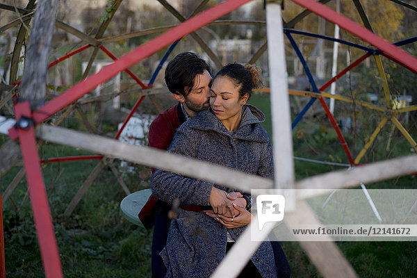 Liebevolles junges Paar im Freien auf einem Spielplatz