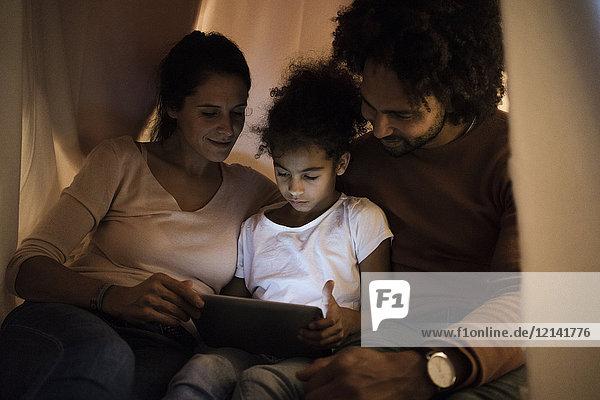 Eltern sitzen im Kinderzimmer mit Tochter und schauen auf das digitale Tablett.