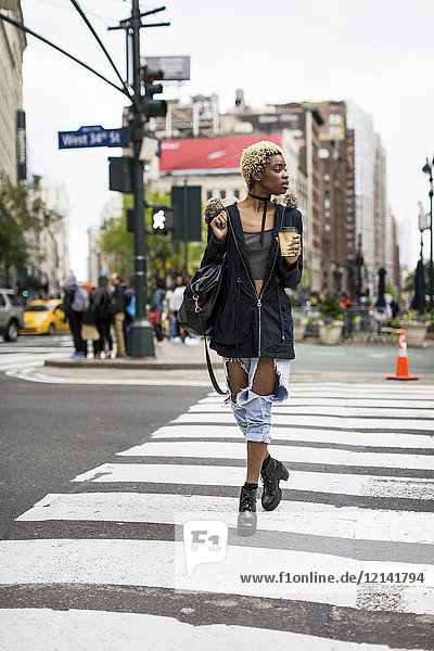USA  New York City  fashionable young woman with coffee to go crossing the street