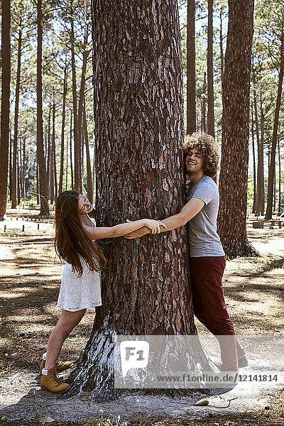 Glückliches junges Paar umarmt einen Baum im Wald