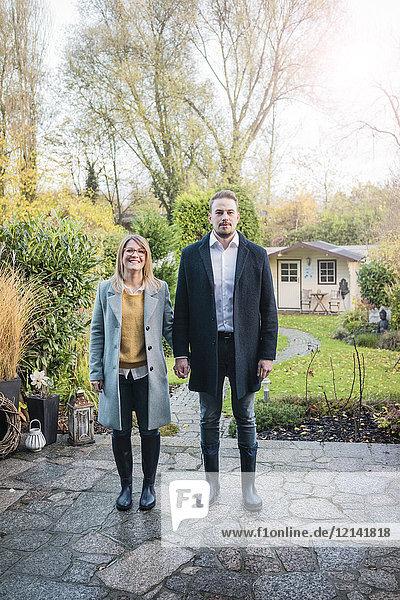 Porträt eines lächelnden Paares auf der Gartenterrasse im Herbst