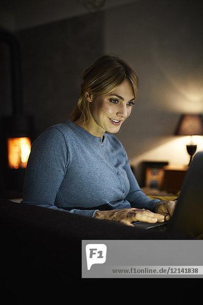 Porträt einer lächelnden Frau am Abend mit dem Laptop zu Hause
