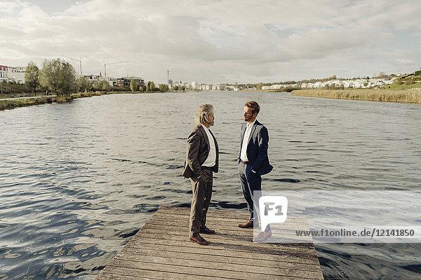 Zwei Geschäftsleute  die auf einem Steg am See stehen und reden.