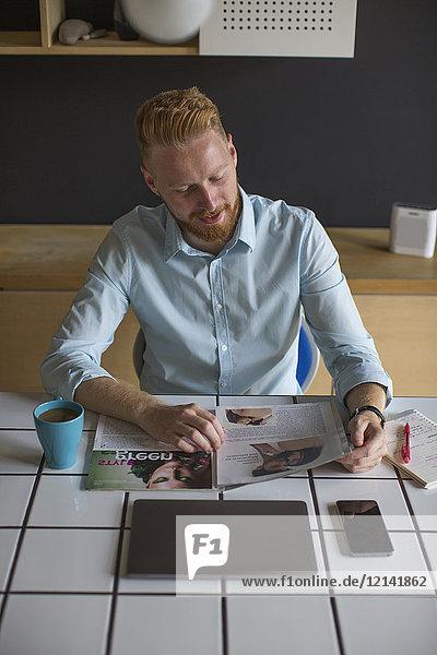 Lächelnder Mann bei Kaffee und Lesemagazin zu Hause