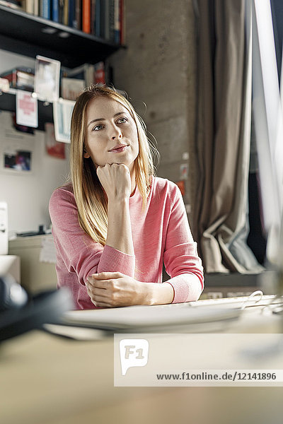 Portrait of young woman working at desk at home