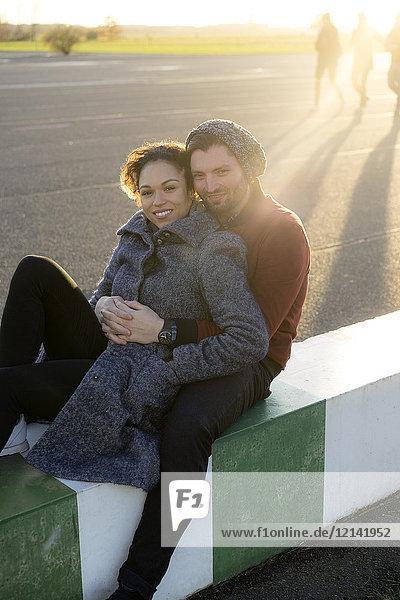 Porträt eines lächelnden jungen Paares  das im Freien sitzt.