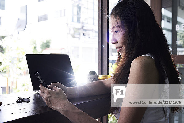 Smiling woman with laptop at the window using cell phone