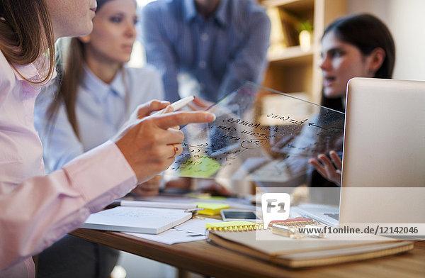 Geschäftsteam diskutiert Formel auf Glasscheibe im Büro