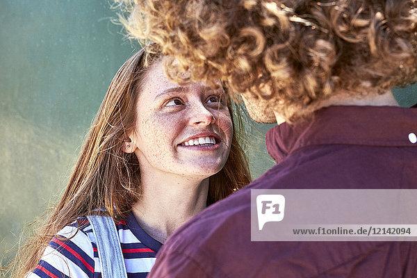 Lächelnde  verliebte junge Frau  die ihren Freund ansieht.