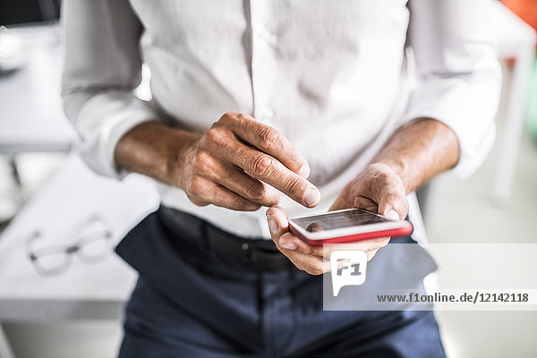 Close-up of businessman using cell phone in office