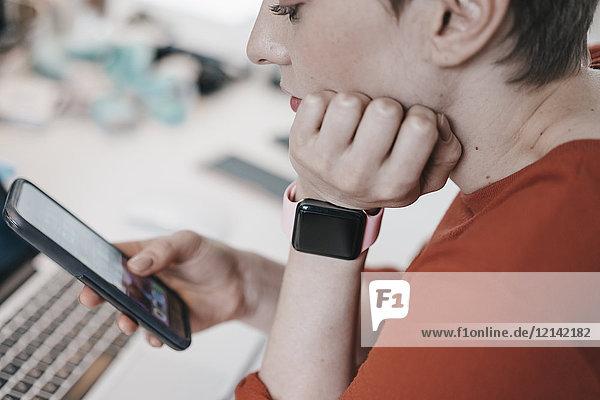 Frau trägt smartwatch mit Handy am Schreibtisch im Büro