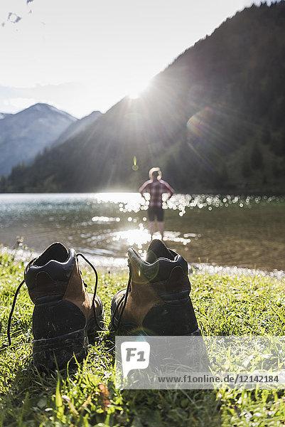 Österreich  Tirol  Wanderschuhe und Frau erfrischend im Bergsee