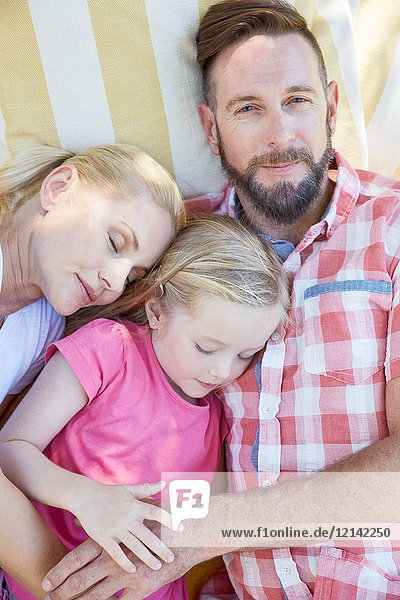 Familie entspannt auf einer Decke liegend