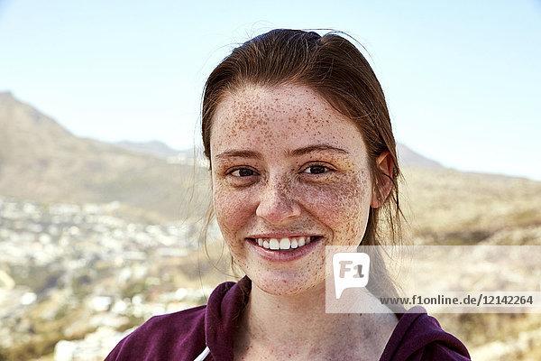 Porträt einer lächelnden jungen Frau mit Sommersprossen im Freien