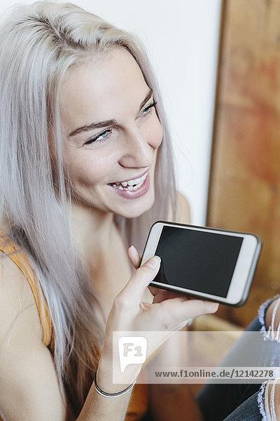 Glückliche junge Frau zu Hause mit Smartphone