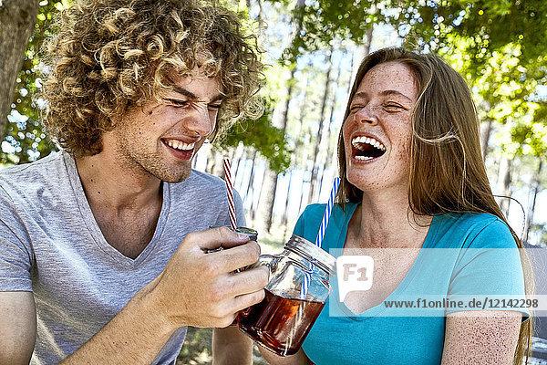 Lachendes junges Paar bei einem Drink im Wald