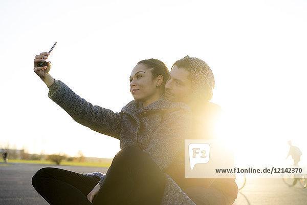 Junges Paar  das bei Sonnenuntergang Selfie nimmt