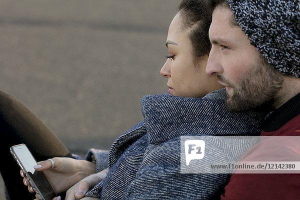 Junges Ehepaar mit Handy in der freien Natur