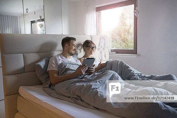 Lächelndes Paar im Bett zu Hause mit Tabletten