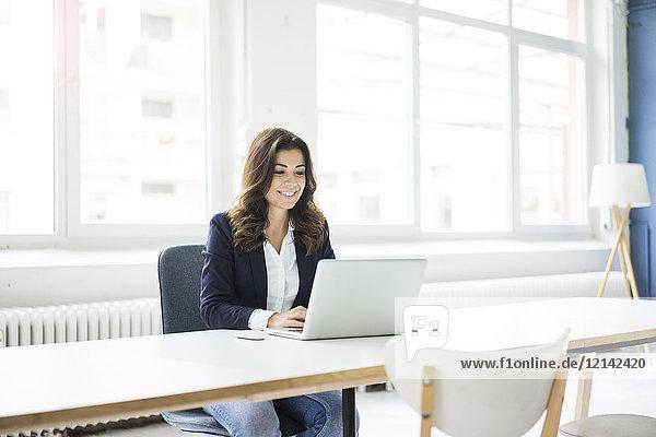 Porträt einer lachenden Geschäftsfrau am Schreibtisch im Büro bei der Arbeit am Laptop