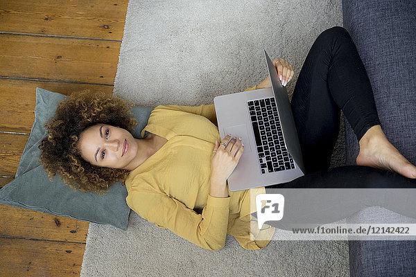 Lächelnde junge Frau zu Hause auf dem Boden liegend mit Laptop