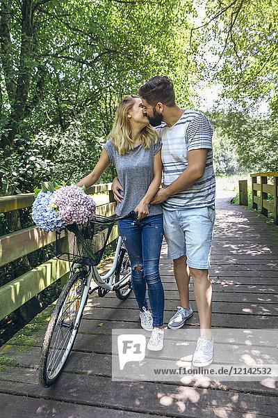 Paar mit Fahrradküssen auf einem Holzsteg in der Natur