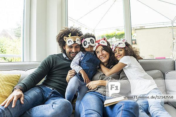 Glückliche Familie  die auf der Couch sitzt und Tiermasken trägt.