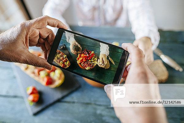 Nahaufnahme von Männerhänden  die ein Foto mit dem Handy machen und Salat von Tomaten  Granatapfel  Papaya und Oliven  mit Papaya mit Früchten an der Seite und mit einem Glas Wein essen.