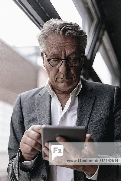 Geschäftsmann  der sich auf das Fenster stützt  mit digitalem Tablett