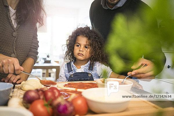Familie backt Pizza in der Küche  Tochter verteilt Tomatensauce