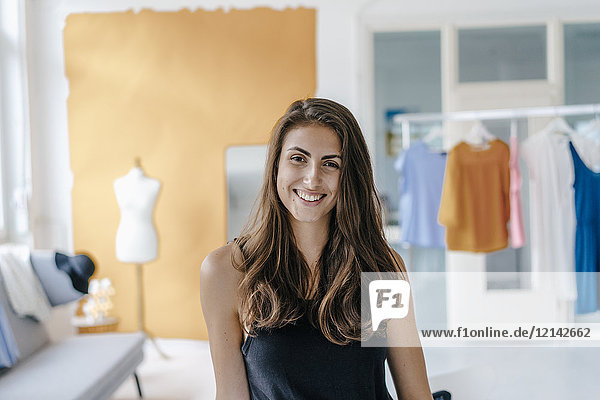 Portrait of happy young woman in fashion studio