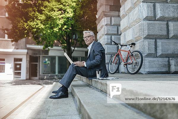 Senior Geschäftsmann auf der Treppe sitzend  mit Laptop