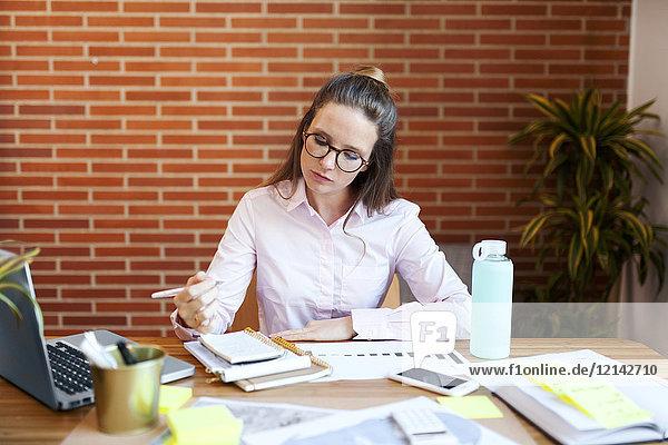 Geschäftsfrau beim Notieren auf dem Tisch im Büro