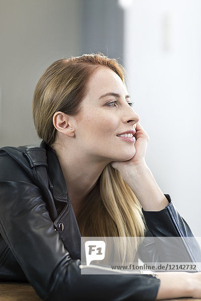Porträt einer lächelnden jungen Frau in Lederjacke