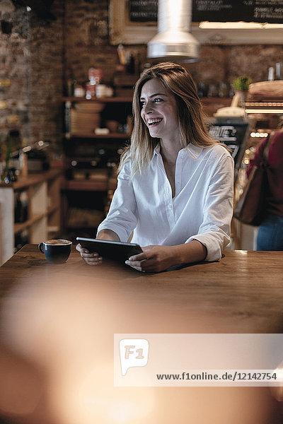 Lachende blonde Frau  die im Café sitzt und Tabletten benutzt.