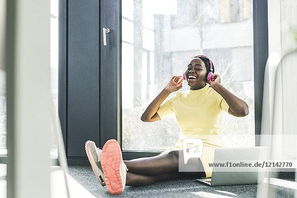 Glückliche Geschäftsfrau sitzt auf dem Boden und hört Musik.