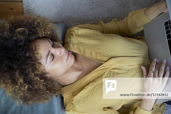 Junge Frau zu Hause auf dem Boden liegend mit Laptop